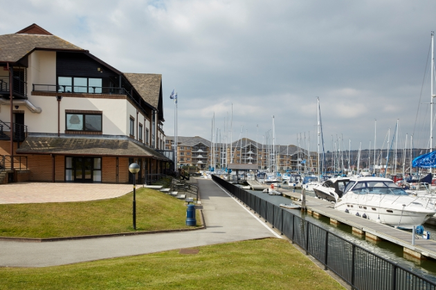The Port House building, grass, and boat dock with boats in