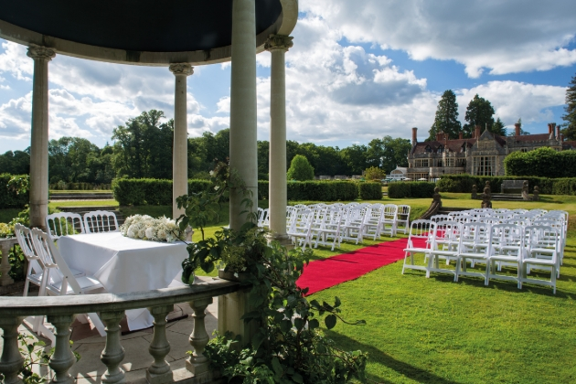 Rhinefield House Hotel, al fresco gazebo for weddings, ceremony chairs set up with red carpet aisle and house in the back ground