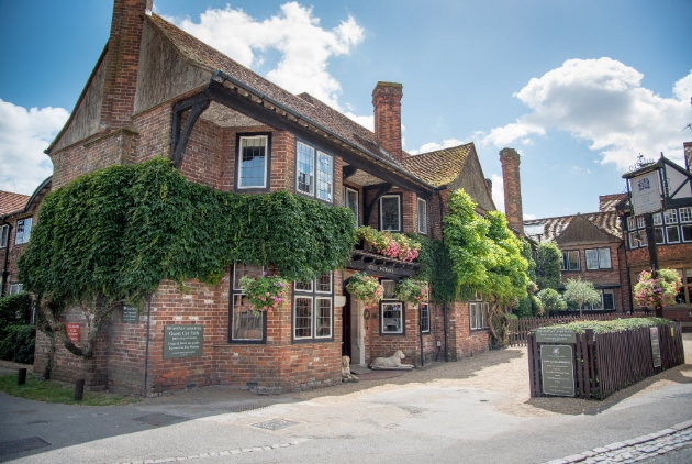 The Montagu Arms Hotel, red brick building close to road covered in ivy