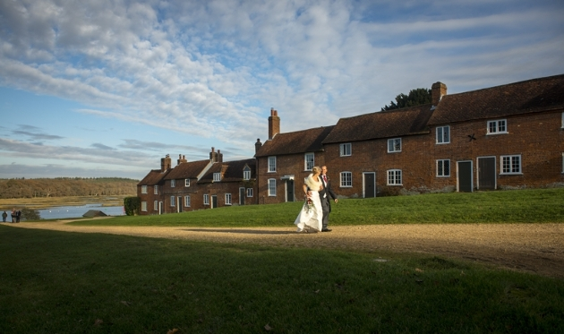 bride and groom walking along path from lake with house running alongside