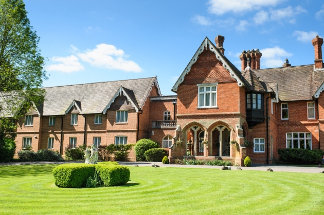 Audleys Wood Hotel, red brick building on manicured lawn blue skies