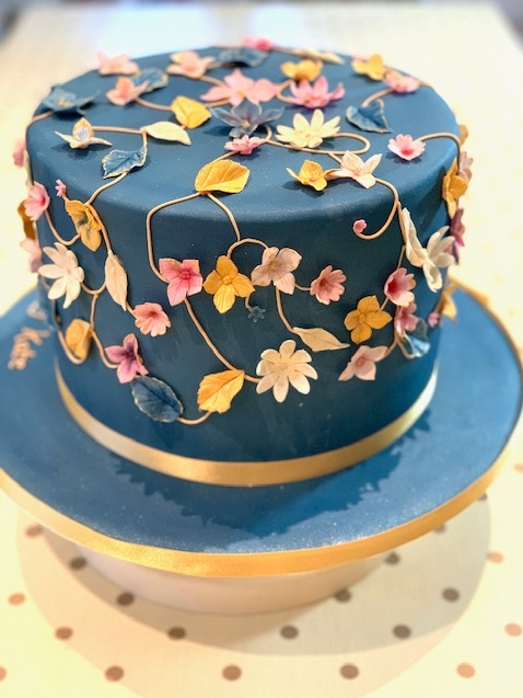 navy blue one tier cake with pink and yellow flowers