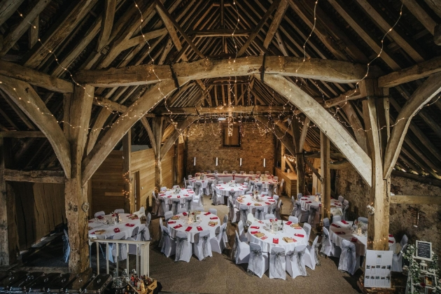 inside of barn set up for a wedding receptions with tables and chairs