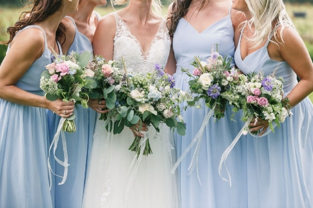 bride and four bridesmaids in blue dresses with posies