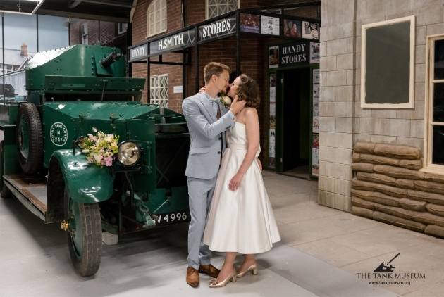 couple in wedding outfits standing in front of vintage vehicle