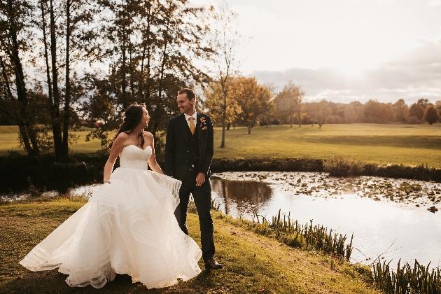 Bride and groom walk by lake